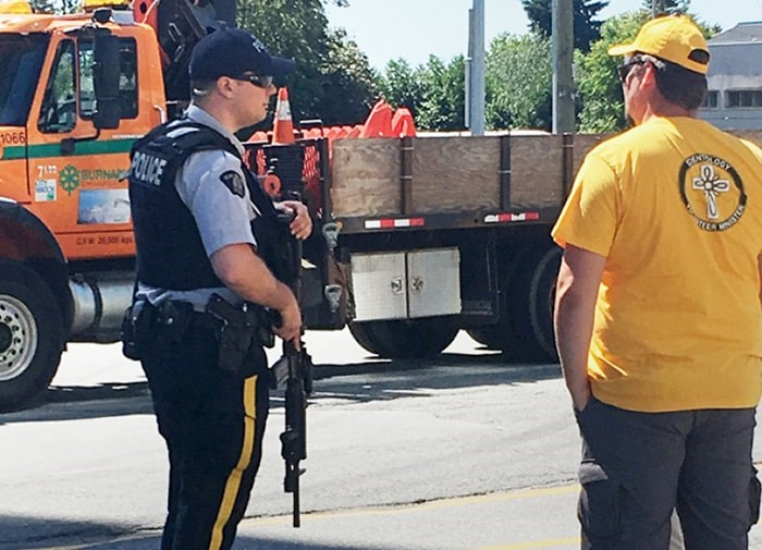 A photo taken at the Edmonds City Fair & Classic Car Show on July 21shows a Burnaby RCMP officer carrying a C8 patrol carbine.