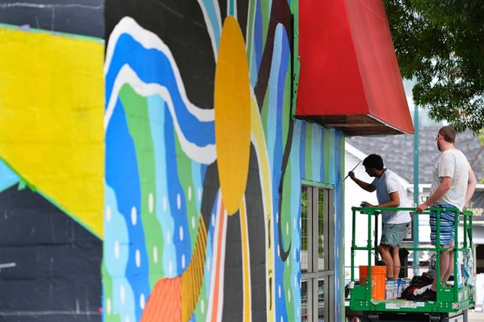 Sonny Green paints as boyfriend Jarod Kingston-Brown looks on. This year's Vancouver Mural Festival starts Thursday and will feature 25 new murals. Photo Jennifer Gauthier