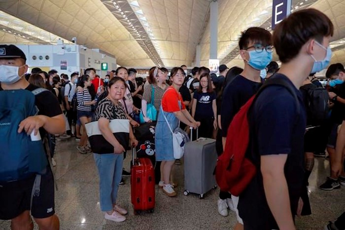 A group of travelers, center, is surrounded by protesters during a protest at the Hong Kong International Airport, Monday, Aug. 12, 2019. One of the world's busiest airports canceled all flights after thousands of Hong Kong pro-democracy protesters crowded into the main terminal Monday afternoon. AP Photo/Kin Cheung