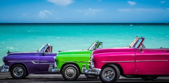 Photo: Havana, Cuba - July 05, 2015: HDR - Three colorfully Chevrolet Cabriolet classic cars parked before the Caribbean Sea on the Malecon in Havana Cuba - Serie Cuba Reportage / Shutterstock