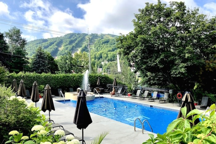 The hills of the Bromont ski area are seen from the pool area at Chateau Bromont in Quebec's Eastern Townships. Photo by Lindsay William-Ross/Vancouver Is Awesome