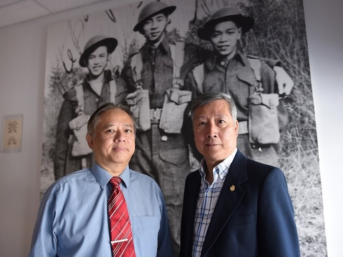 Glen Wong and King Wan, the president of the Chinese Canadian Military Museum Society. In the background is a photo with Glen's father Bing Chew Wong on the far left. Photo by Dan Toulgoet