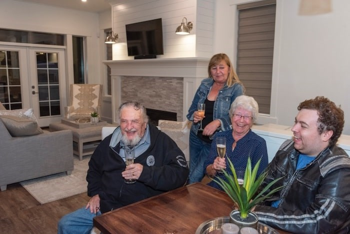 Albert Prendergast of Port Moody, the winner of the 2019 PNE Prize Home Grand Prize Package, celebrates in the house last night (Monday) with his partner, Maureen Newell, and daughter-in-law Laurie Newell and grandson Kyle Newell. Photo courtesy PNE