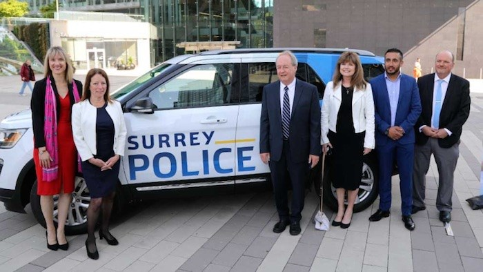 Members of Surrey City Council stand in front of a conceptualized Surrey Police Department vehicle on May 7, 2019. Photo via Surrey.ca