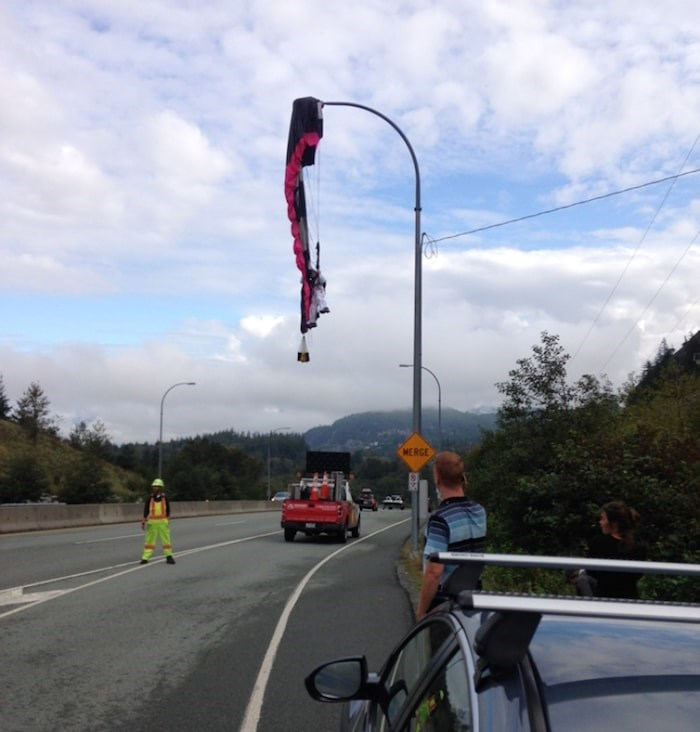 A paraglider is seen dangling from a lamppost over a lane of Highway 99 in Squamish on Tues. Sept 10, 2019. Photo submitted/via The Squamish Chief