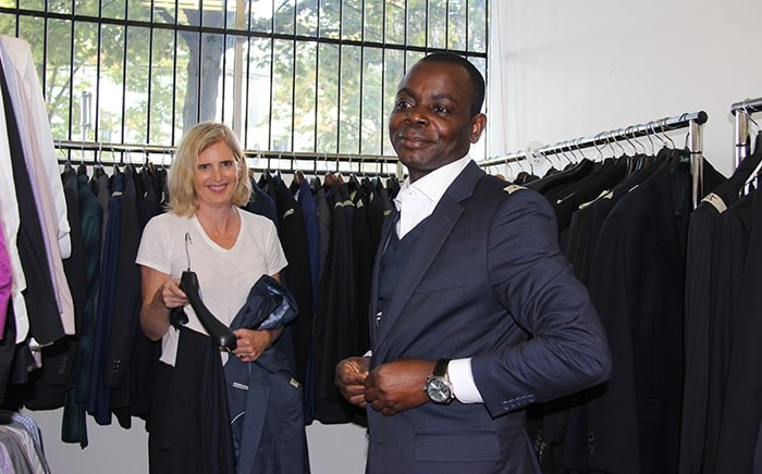 Joan Glover helps client Michael Olabode pick out a suit. Photo: Elisia Seeber