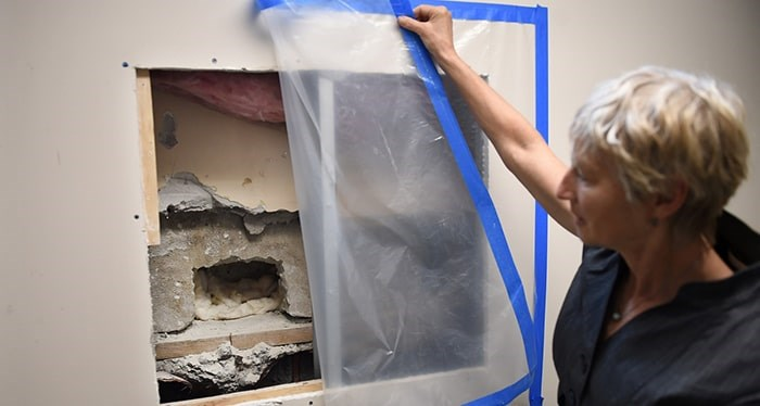Principal Janet Souther shows where tradespeople decided to access the capsule via a stairwell and behind several layers of cement and drywall from systemic upgrades. Photo Dan Toulgoet