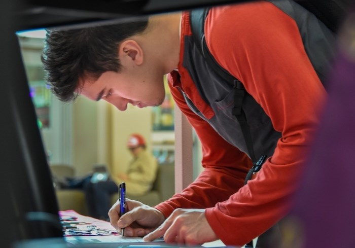 Douglas College student Jonah Roesler, 22, signs a pledge to vote in the upcoming federal election. Photo by Stefan Labbé/Tri-City News