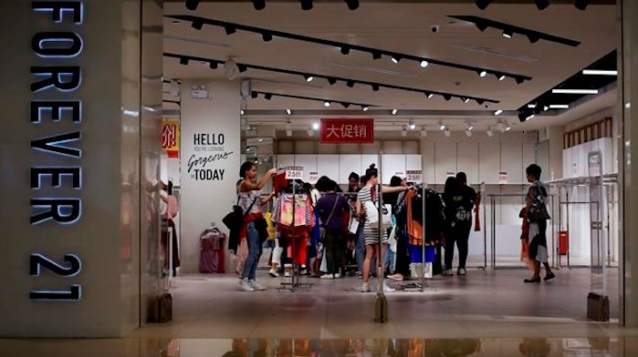 FILE - In this Tuesday, May 7, 2019, file photo, women select clothing at an American fast fashion retailer Forever 21 which is offering clearance discounts at a shopping mall after it pulled out from China's market, in Beijing. Low-price fashion chain Forever 21, a one-time hot destination for teen shoppers that fell victim of its own rapid expansion and changing consumer tastes, announced Sunday, Sept. 29, 2019, that it has filed for Chapter 11 bankruptcy protection. AP Photo/Andy Wong, File