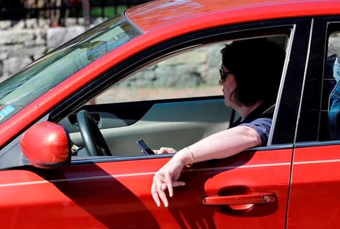 In this Thursday, May 16, 2019 photo, a driver uses his cell phone while driving in Portland, Maine. The son of a 71-year-old senior ticketed for distracted driving says the $368 citation issued to his mother has been cancelled by Vancouver police, and the department has also apologized. THE CANADIAN PRESS/AP-Robert F. Bukaty