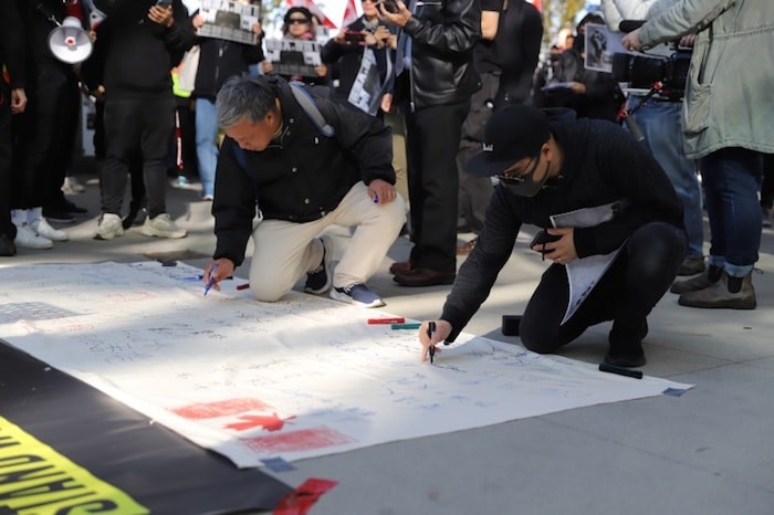 Supporters also wrote messages of support for Hong Kong protesters on a large white banner which will be taken back to Hong Kong. Photo by Herb Chao