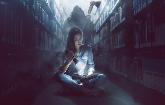 To get you into the mood for things that lurk in the dark, VPL's reading experts have rounded up this list of top picks for all monster fans. Photo: Reading scary book in library/Shutterstock
