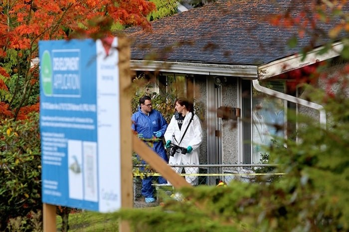 The Mounties are conducting an internal review following the deaths of an eight-year-old boy and his father last week in Coquitlam. Photo: Homicide investigators gathered evidence from a home at 719 Seaton Avenue in Coquitlam on Oct. 23. Mario Bartel/Tri-City News