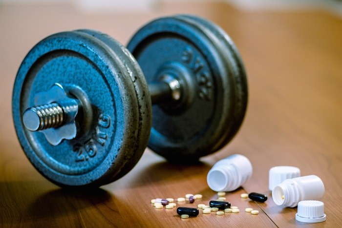 A North Vancouver bodybuilder has been fined just under $140,000 and placed under house arrest for four months as part of his sentencing in a steroids trafficking case. Photo: Steroid pills and weights/Shutterstock