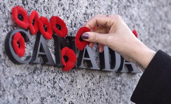People place poppies over lettering in the National War Memorial during the National Remembrance Day ceremony in Ottawa on November 11, 2016. A new survey suggests more Canadians are planning to mark Remembrance Day this year, perhaps in a salute to the few remaining veterans of the Second World War. THE CANADIAN PRESS/Justin Tang