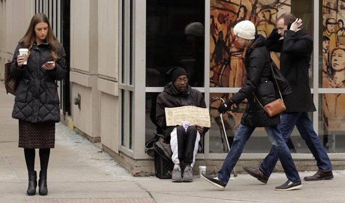 A man, center, panhandles on the street Monday, Jan. 25, 2016, in Chicago. A bylaw targeting certain panhandlers has been approved in the Metro Vancouver city of Maple Ridge. THE CANADIAN PRESS/AP-M. Spencer Green