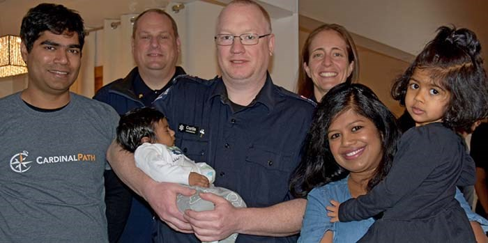 Baby Arthur, held by paramedic Curtis Rasmussen, with (left to right) father Anish John, paramedics Jason Davies and Sami Lingren, and mother Jasmine Anish John with daughter Viola Scarlette John, 3. Missing is paramedic Michella McCaskill.