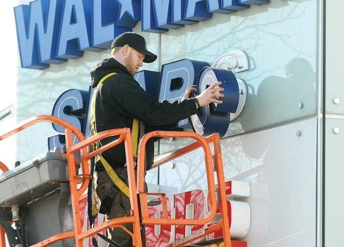 In this 2012 file photo, a worker upgrades the Sears sign at Capilano Mall. The mall's management is now going public with plans to redevelop the site. file photo Cindy Goodman, North Shore News