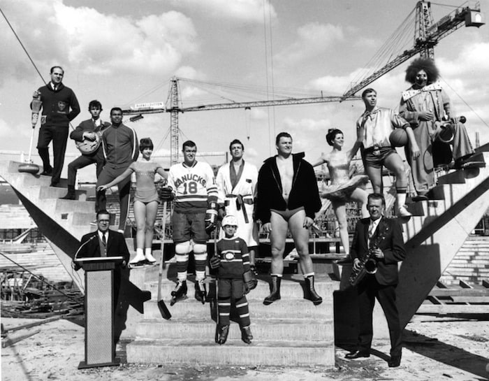 Athletes and performers representing future uses of the Pacific Coliseum standing in the construction site in 1967. Harry Jerome (third from left), Karen Magnussen (fourth from left), Barry Watson (fifth from left, in Canucks jersey) and Gene Kiniski (fourth from right).