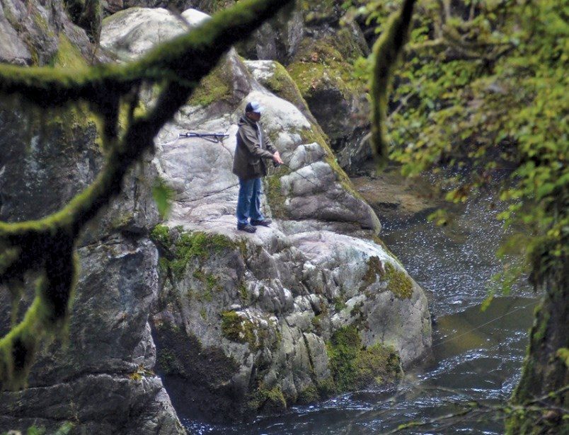 An angler casts his line in the Capilano River in the days after the 2020 Cleveland Dam tragedy. / Paul McGrath, North Shore News files.