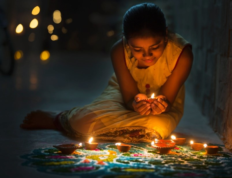 a-girl-lights-diya-clay-lanterns-during-diwali-the-hindu-celebration-of-light