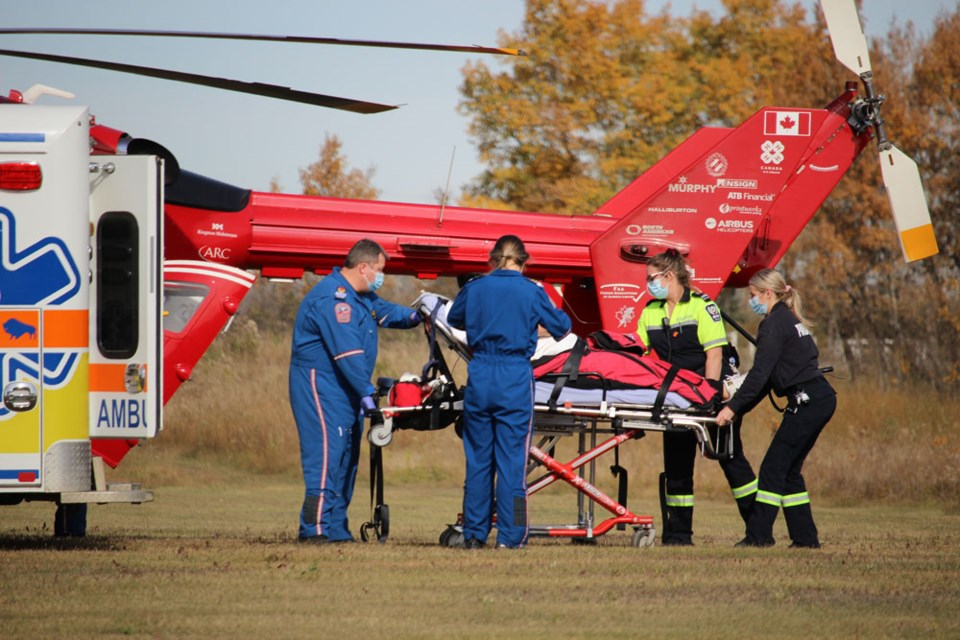 STARS air ambulance and Hamiota ambulance EMT staff work together to transfer a patient into the medical helicopter.