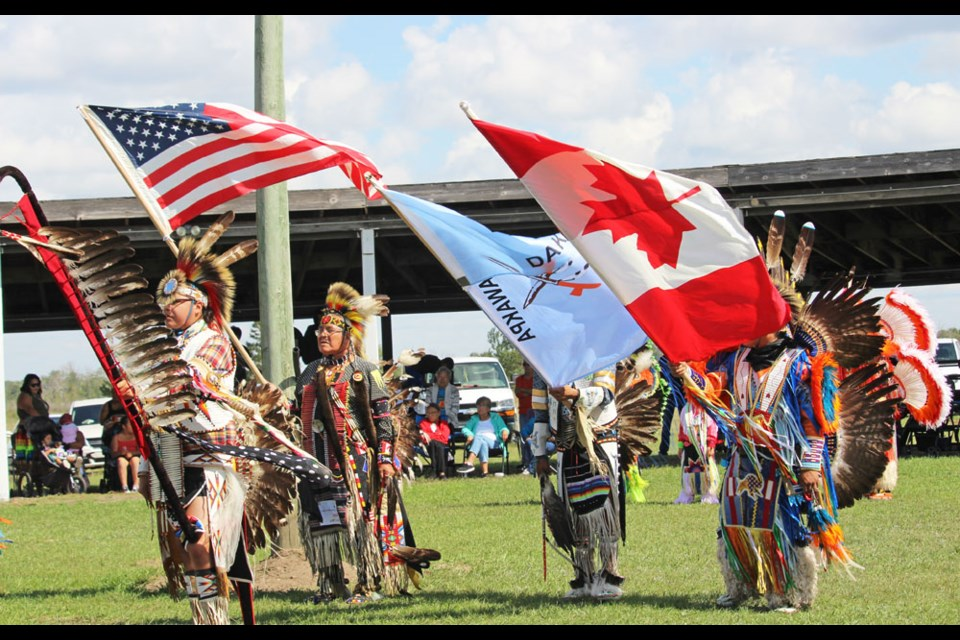 The Dakota Flag, Canadian and American Flags, and the eagle feather staff are part of the opening ceremonies at Canupawakpa Dakota Nation Wacipi (pow wow) on Sept. 4. At this time veterans who served in all wars, conflicts and peacetime are mentioned.