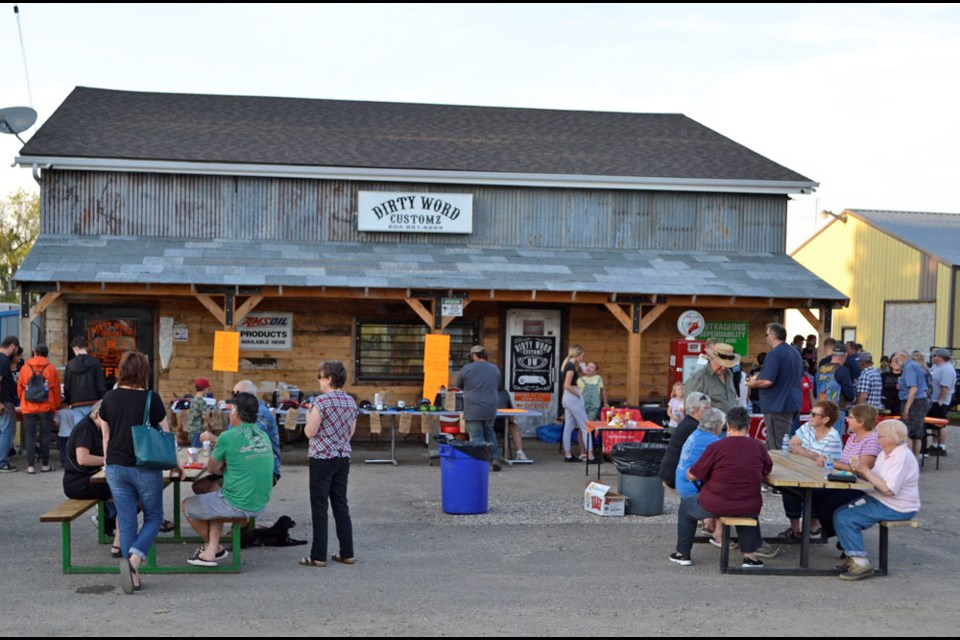 A crowd enjoys cars, conversation and a barbeque in Oak Lake at Wiltshire's business location.