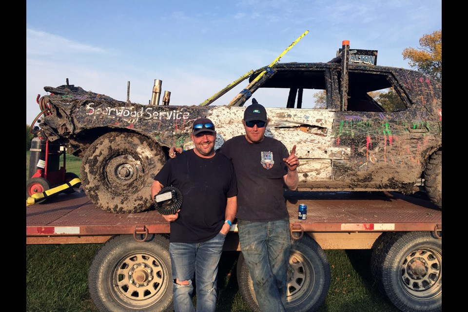 Virden's Jody Braybrook (l) took first place in the Crunch Bowl Demolition Derby at Crystal City Sunday, Sept. 19. With the help of his mechanic Kris Hay (r), Braybrook brought home prize money, as well as a top place trophy.